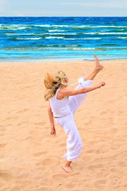 woman-kicking-air-on-beach-